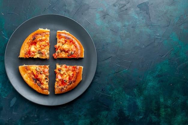 Vista dall'alto della pizza al formaggio quattro fette all'interno della piastra sulla superficie blu scuro