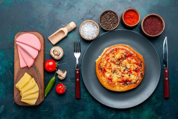 Vista dall'alto del tondo di pizza al formaggio formato con formaggio condimento sulla superficie blu scuro