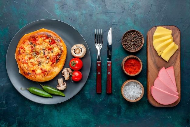 Vista dall'alto della pizza al formaggio con condimenti di verdure e formaggio sulla superficie blu scuro
