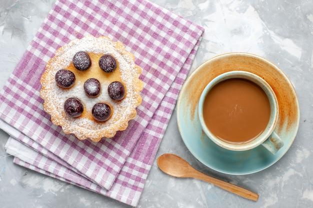 Vista dall'alto piccola torta di ciliegie zucchero in polvere con caffè al latte sullo sfondo grigio zucchero torta biscotto dolce