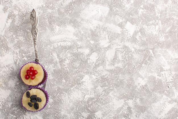 Вид сверху маленькие шоколадные пирожные с клюквой на светлом столе, печенье, сахар, сладкое тесто