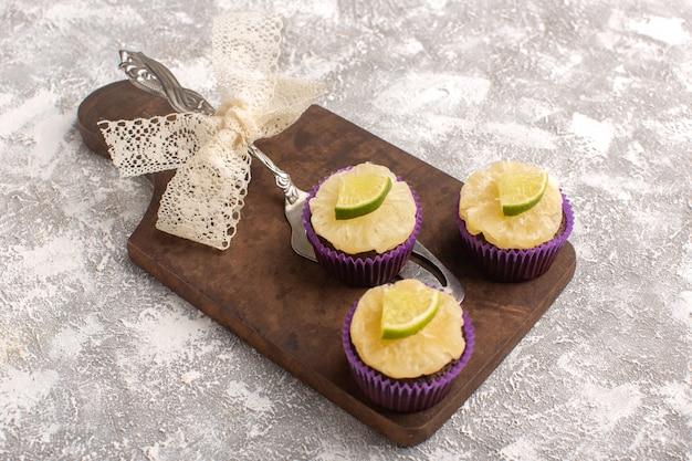 トップビュー明るい背景に新鮮なスライスレモンと小さなチョコレートケーキケーキビスケット砂糖甘い焼き生地