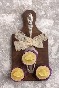 トップビュー明るい背景にレモンスライスと小さなチョコレートケーキケーキビスケット砂糖甘い焼き生地