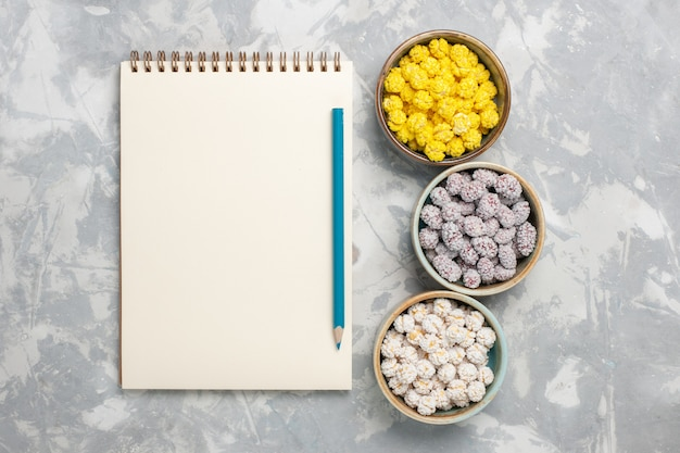 Vista dall'alto piccole caramelle colorate all'interno di pentole sulla superficie bianco-chiaro caramelle dolci bonbon torta biscotto zucchero
