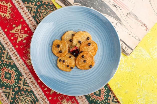 Вид сверху маленькое печенье внутри синей тарелки на желтом столе, выпечка сладкого чая
