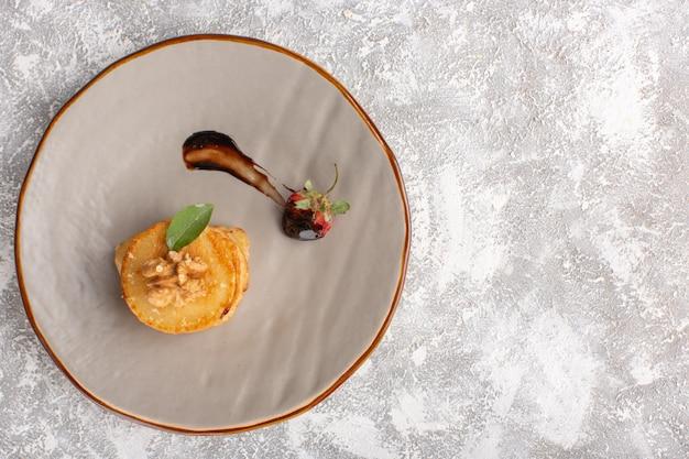 Вид сверху маленькое печенье внутри тарелки на светлом столе, выпечка из сладкого печенья с сахаром