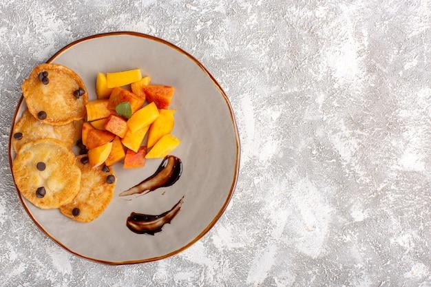 Вид сверху маленькие печенья внутри тарелки со свежими нарезанными персиками на светлом столе, выпечка из сладкого бисквитного торта