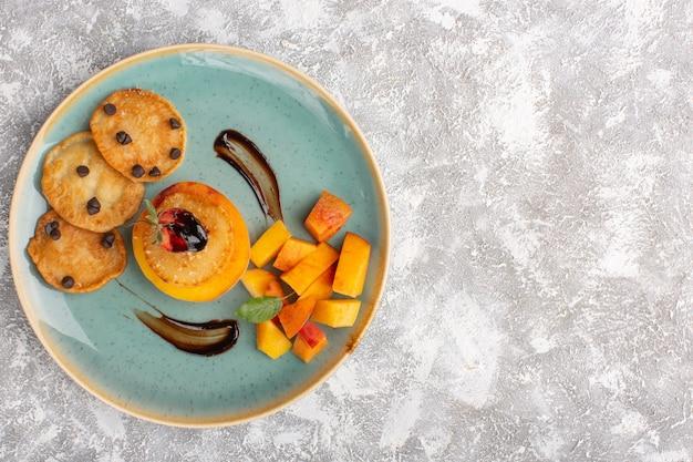 Вид сверху маленькие пирожные внутри тарелки со свежими нарезанными персиками на светлом столе, пирожное бисквитное сахарное тесто