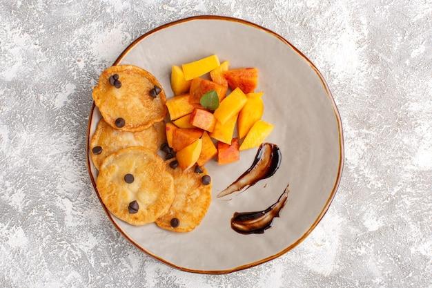 Вид сверху маленькие печенья внутри тарелки со свежими нарезанными персиками на светлом столе, сладкая выпечка из сахарного торта