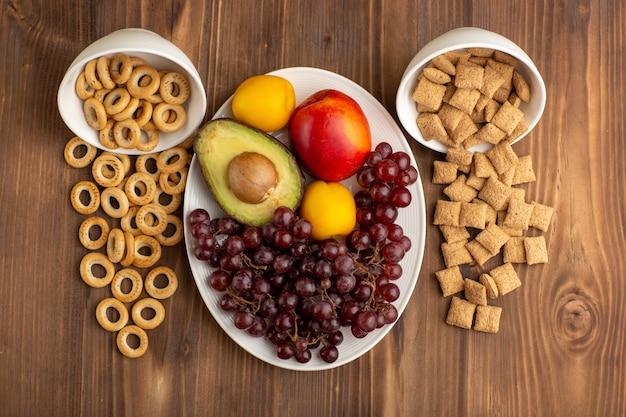茶色の木製の机の上の果物と小さなクッキーとクラッカー