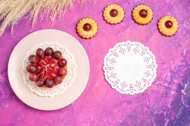 Вид сверху маленькое печенье с тортом на розовом столе сладкий бисквитный торт десерт