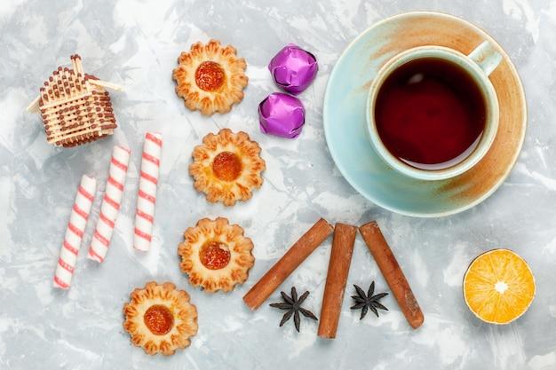 明るい白い机の上にシナモンとお茶と一緒に小さなクッキーを上から見る