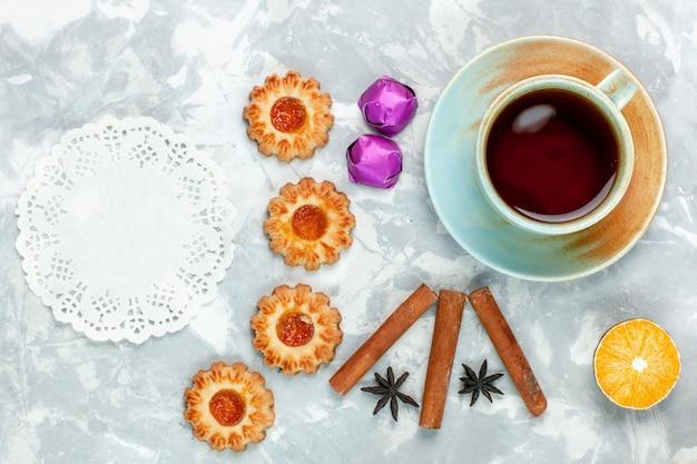 Vista dall'alto piccoli biscotti con cannella e tè su una superficie bianca chiara