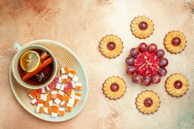 Вид сверху маленькое печенье с чашкой чая на коричневом столе, десерт из сладкого бисквитного торта