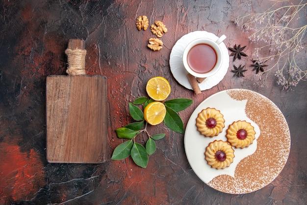 Vista dall'alto piccoli biscotti con una tazza di tè sulla torta di biscotto zucchero da tavola scuro