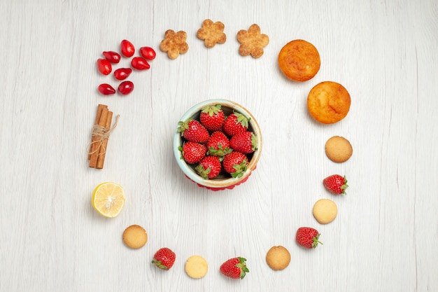 白い机の上に新鮮な果物と小さなクッキーの上面図