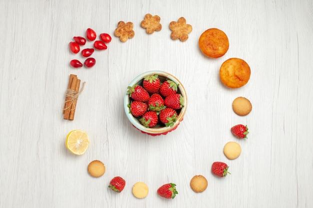 Vista dall'alto piccoli biscotti con frutta fresca sulla scrivania bianca