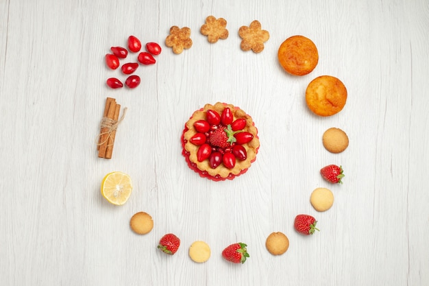 白い机の上にフルーツとケーキと小さなクッキーの上面図