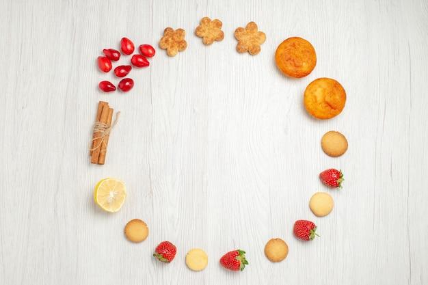 白い机の上に果物と小さなクッキーの上面図
