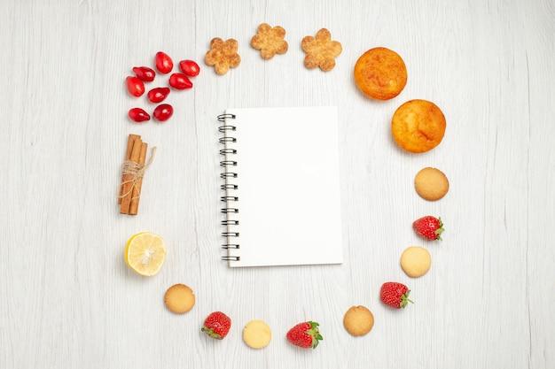 Vista dall'alto piccoli biscotti con frutta sulla scrivania bianca