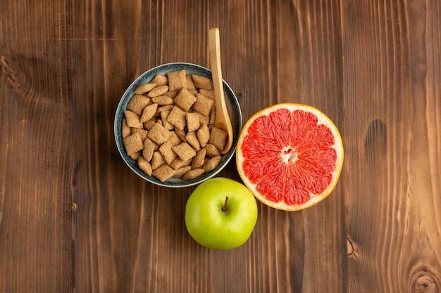 Vista dall'alto piccoli biscotti con pompelmo e mela sullo scrittorio di legno marrone