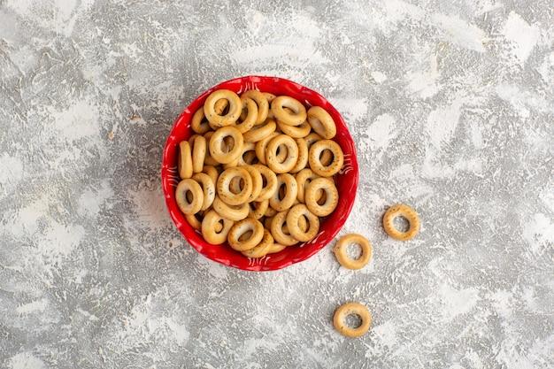 Вид сверху маленькие крекеры внутри красной тарелки на белой поверхности