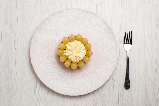 Vista dall'alto piccola torta alla crema con uva fresca su superficie bianca torta alla frutta dolce biscotto biscotto