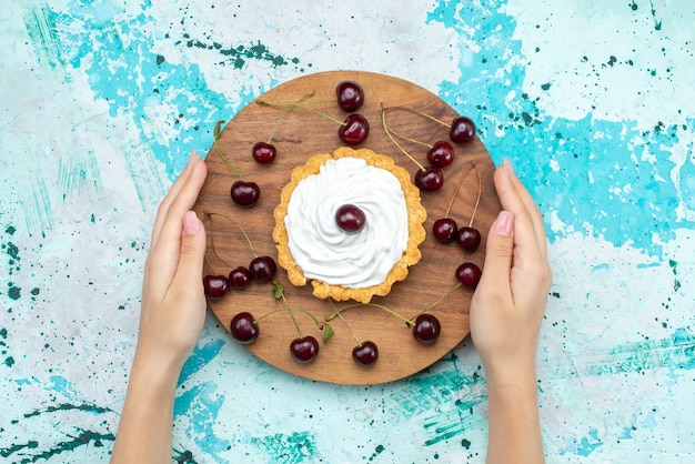 Top view little cream cake with fresh sour cherries on the light-blue table cake cream fruit bake sweet