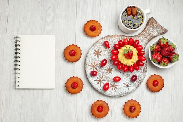 白い机の上にフルーツとケーキとトップビューの小さなクリームケーキ