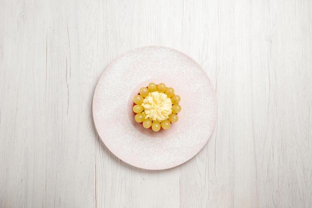 上面図白い机の上のブドウと小さなクリームケーキフルーツケーキデザートパイビスケットクッキー