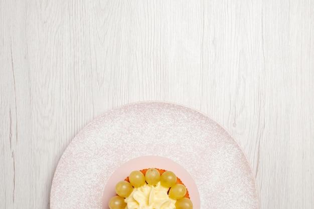 上面図白い表面にブドウと小さなクリームケーキフルーツケーキデザートパイビスケットクッキー