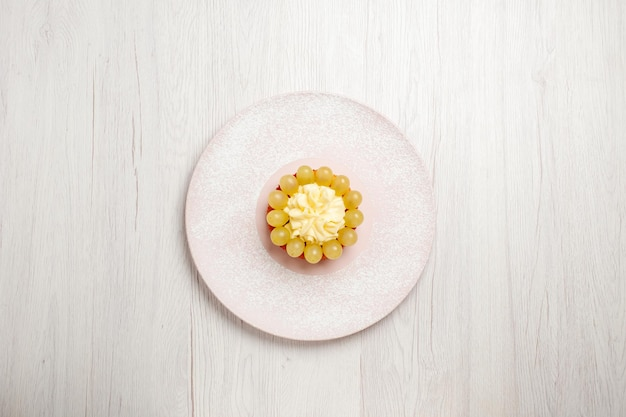 Vista dall'alto piccola torta alla crema con uva su una scrivania bianca torta alla frutta torta dolce biscotto biscotto