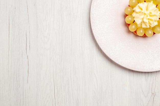 Vista dall'alto piccola torta alla crema con uva su superficie bianca torta alla frutta torta dolce biscotti biscotti