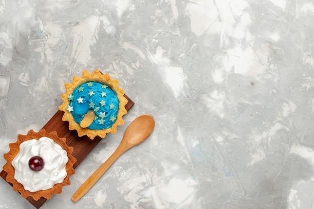 Вид сверху маленькие кремовые пирожные на светлом столе, крем для торта, выпечка сладкого чая