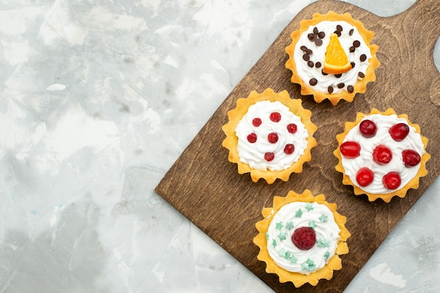Top view little cream cakes with fruits on the light grey surface sugar sweet