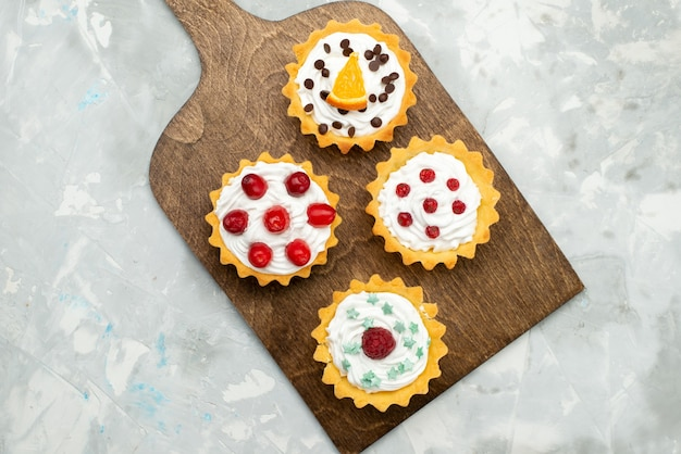 Вид сверху маленькие кремовые пирожные с фруктами на светло-серой поверхности сладкого сахара