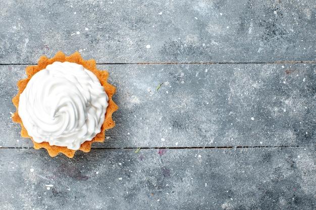 Vista dall'alto piccola torta cremosa al forno deliziosa isolata sullo sfondo grigio torta biscotto zucchero dolce
