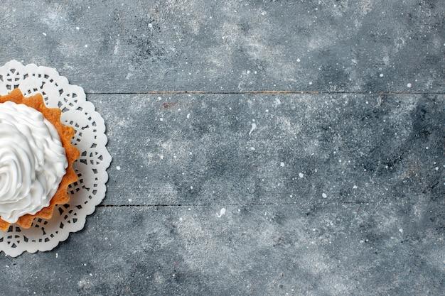 Vista dall'alto piccola torta cremosa al forno delizioso isolato su sfondo grigio chiaro torta biscotto dolce crema di colore cuocere