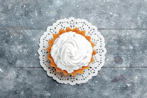 Vista dall'alto piccola torta cremosa al forno delizioso isolato su sfondo grigio chiaro torta biscotto dolce crema di zucchero
