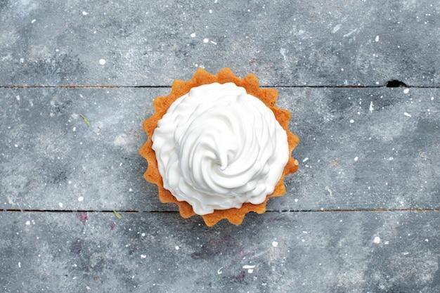 上面図灰色の背景のケーキビスケット甘い砂糖の写真に分離されたおいしい焼きたての小さなクリーミーなケーキ