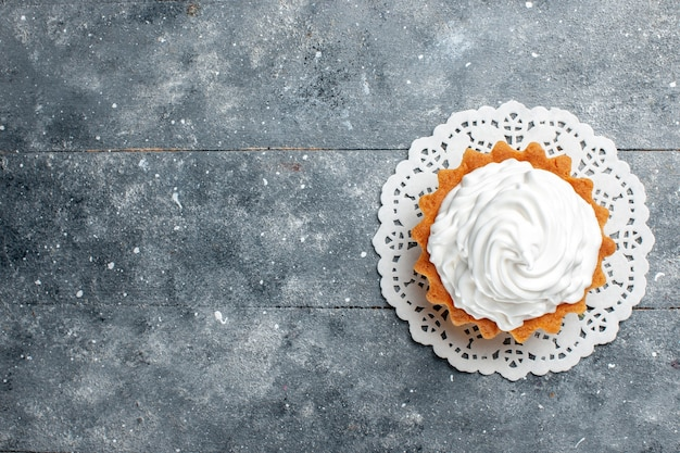 Вид сверху маленький сливочный торт, испеченный вкусно изолирован на сером светлом фоне торт бисквит сладкий сахарный крем выпечка