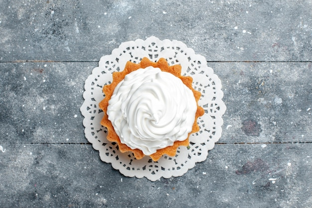上面図灰色の明るい背景のケーキビスケット甘い砂糖クリームに分離されたおいしい焼きたてクリーミーなケーキ