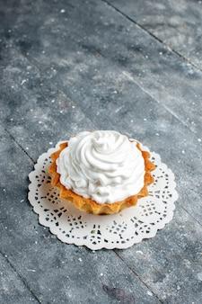 Вид сверху маленький сливочный торт, испеченный восхитительно, изолированный на сером светлом столе, торт, бисквит, сладкий цвет, крем, сахар