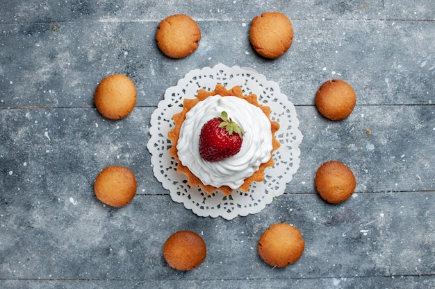Top view little creamy cake baked delicious isolated with strawberry along with cookies on the grey light desk cake biscuit sweet color cream sugar