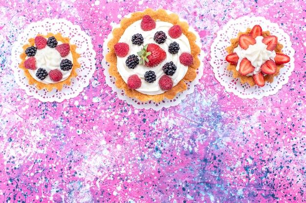 Vista dall'alto piccola torta cremosa con frutti di bosco sullo sfondo bianco chiaro torta biscotto bacca dolce cuocere foto