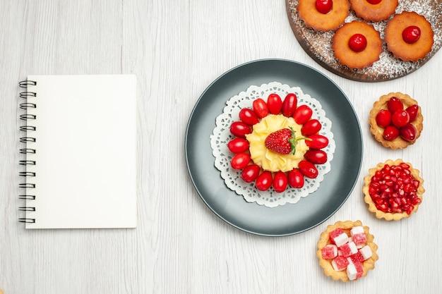 上面図白い机の上にケーキや果物と小さなクリーミーなケーキ