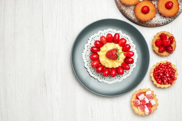 Vista dall'alto piccola torta cremosa con torte e frutta sulla scrivania bianca