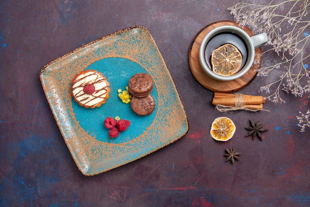 Вид сверху маленький сливочный торт с шоколадным печеньем и чашкой чая на темной поверхности бисквитного торта сладкий пирог сахарное печенье