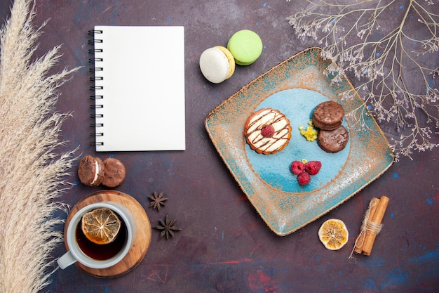 Вид сверху маленький сливочный торт с шоколадным печеньем и чашкой чая на темной поверхности бисквитного сладкого пирога сахарного печенья