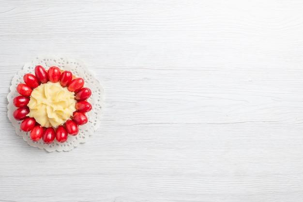 白い机の上にハナミズキと小さなクリーミーなケーキの上面図